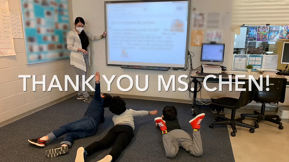 """A photo of a teacher standing my a SMART board while three students, facing the board, are lying on their stomach. In the middle of the photo is the text """"Thank you Ms. Chen!""""."""