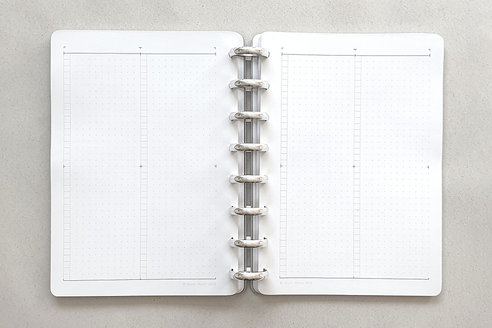 A discbound notebook with printed white sheets bound in it that have a dot grid and vertical squares in a checklist style. The binding discs are shiny aluminium. The background is textured grey recycled paper.