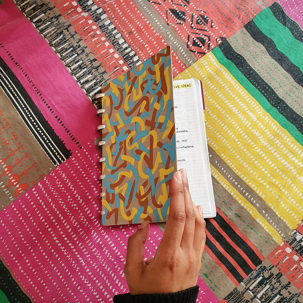 A discbound notebook with an abstract handpainted cover. A hand is opening the notebook, showing part of a page of notes inside titled 'Ideas'. The notebook is on a colourful patterned background.