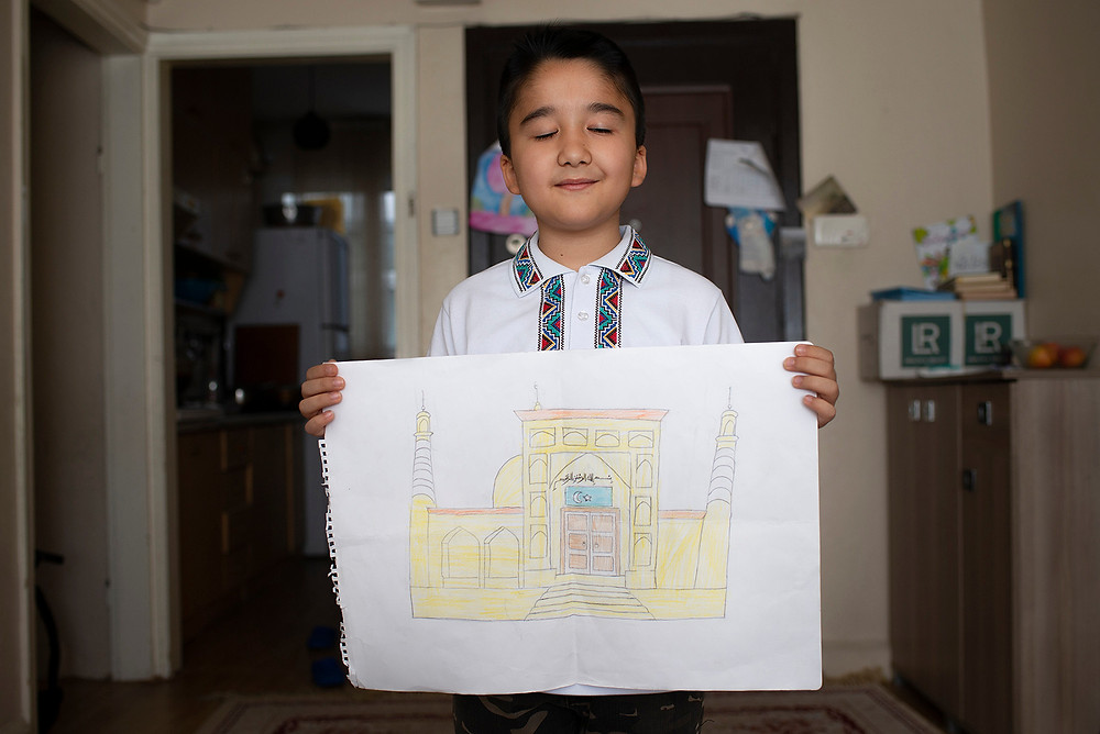 Ten-year-old Bilal Habibulla poses with his drawing of the Id Kah Mosque in Kashgar, Xinjiang, at his home in Istanbul on April 27. The Id Kah Mosque is a symbol for the Uighur culture. [Roxi Pop for Foreign Policy]