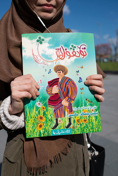 The Uighur teacher and poet Muyesser Abdulehed holds a copy of Four-Leaf Clover, the first literary magazine abroad written by Uighur children for Uighur children, on April 21. [Roxi Pop for Foreign Policy]