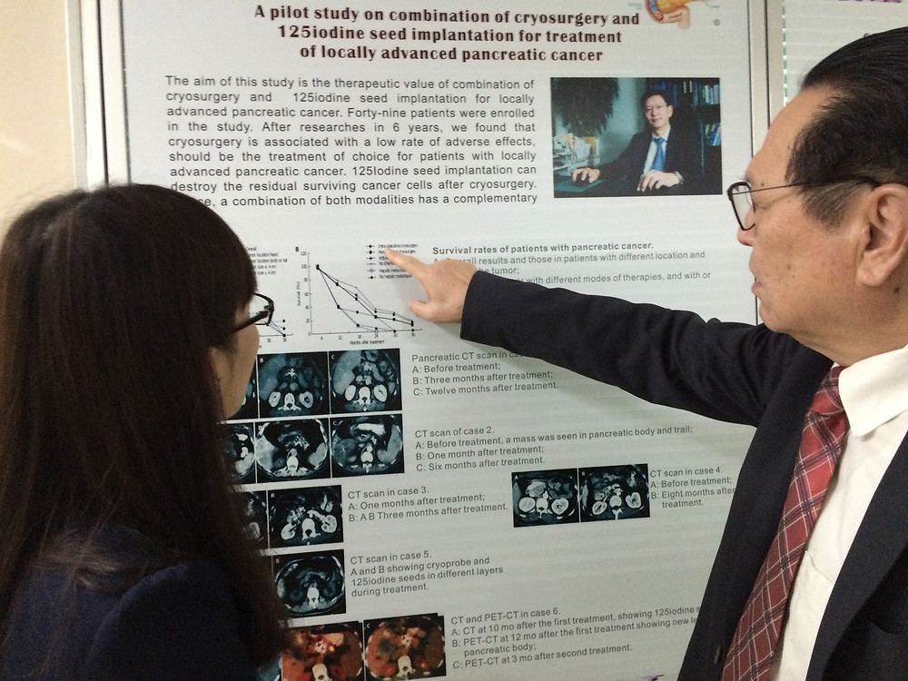 Xu Kecheng points to a poster describing one of Fuda Cancer Hospital's clinical trials [Simina Mistreanu/Al Jazeera]