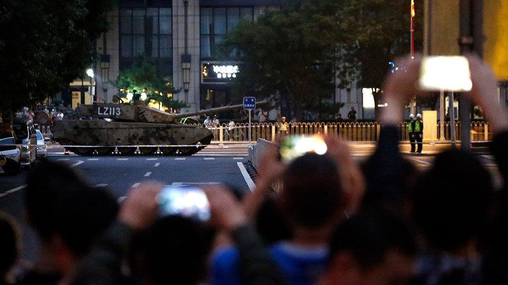Bystanders take photos as an armoured military vehicle passes along a street in Beijing during rehearsals for the October 1 festivities. but the public will mostly have to watch the day's events on television. [Mark Schiefelbein/AP Photo]