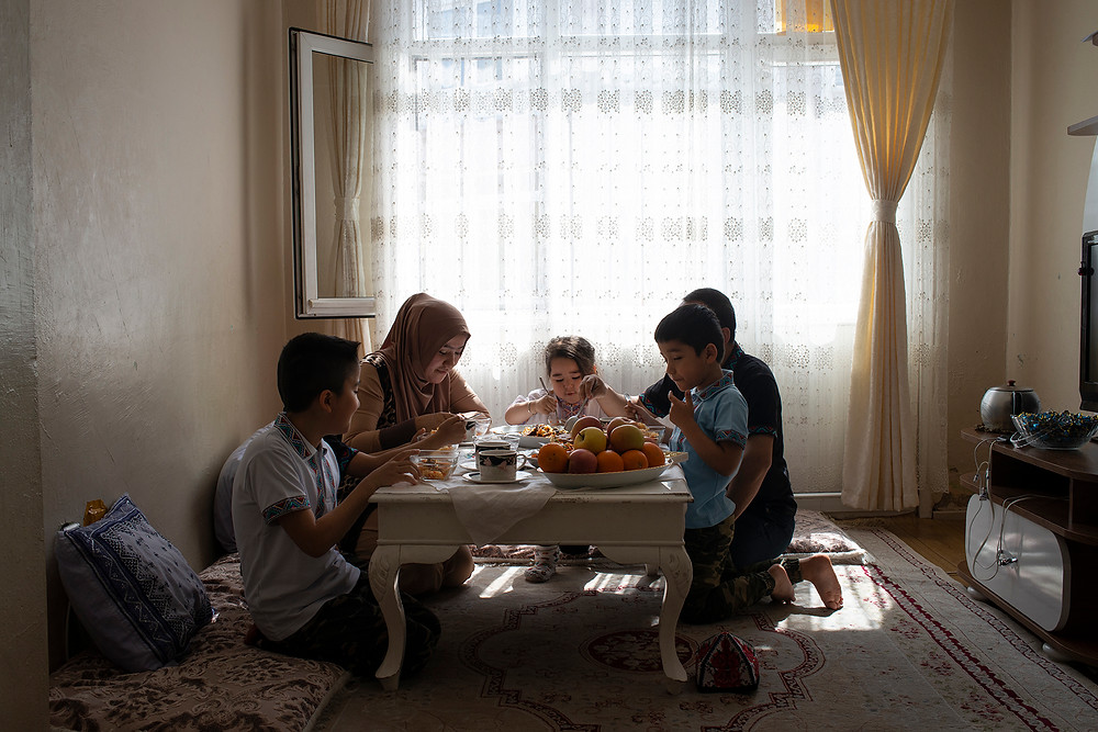 Habibulla Muhemmet and Mihriban Abduweli have breakfast with their family in the living room of their small apartment in the Faith neighborhood of Istanbul on April 27. [Roxi Pop for Foreign Policy]