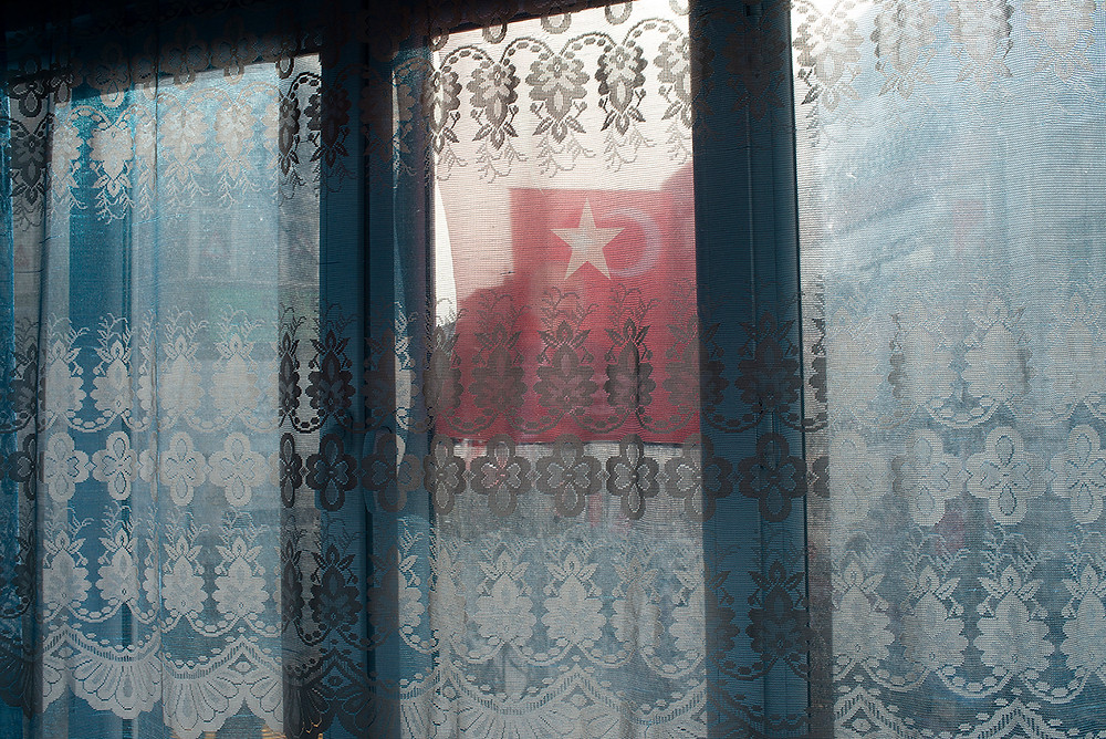 The Turkish flag is seen through the apartment window of Yusuf Sulaiman, a Uighur musician who now lives in Istanbul, on April 24. [Roxi Pop for Foreign Policy]