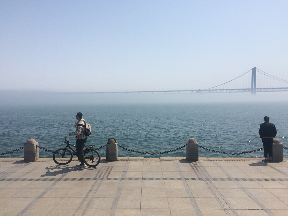 Passers-by look on near Dalian's Xinghai Square [Simina Mistreanu/dpa]