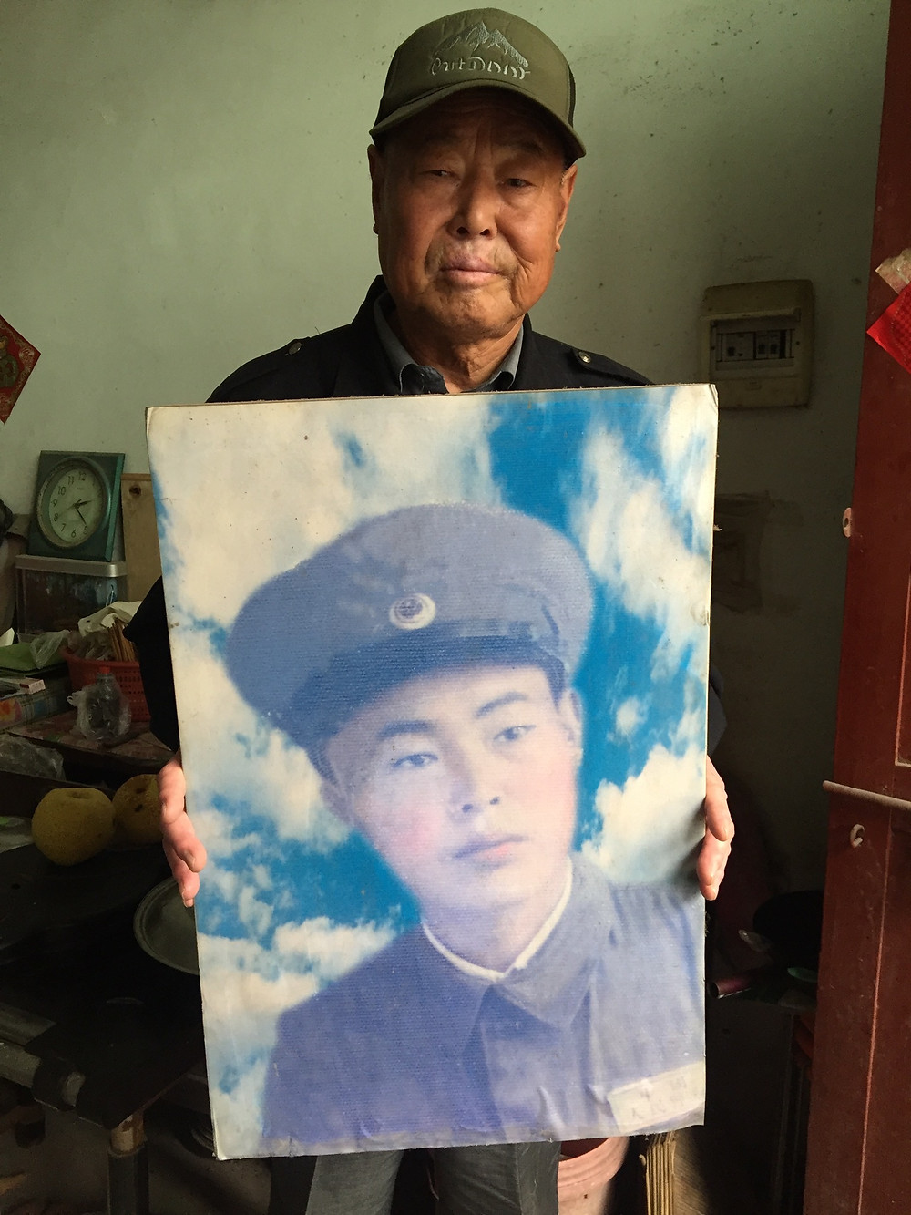 Xiao with a portrait of himself as a young soldier in the Chinese army in the 1950s. Photo by Simina Mistreanu/dpa