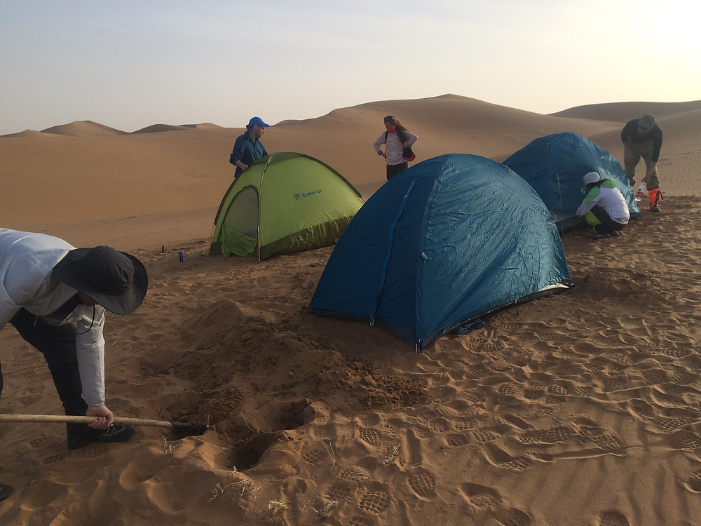 Dave Brackett, a hiker from Beijing, attempts to protect his tent against the wind in the Tengger Desert. Photo: Simina Mistreanu