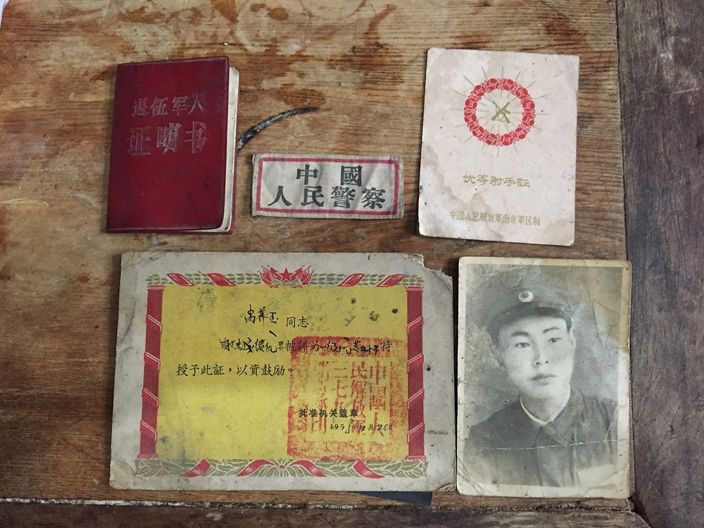 """Xiao Yangyu's People's Liberation Army certificate and badge, as well as two """"best shooter"""" certificates from the 1950s are displayed on a table in his home. Xiao came of age with the establishment of the People's Republic of China and lived through decades of famine, politically fuelled violence and traumatically enforced population-control policies. Photo by Simina Mistreanu/dpa"""