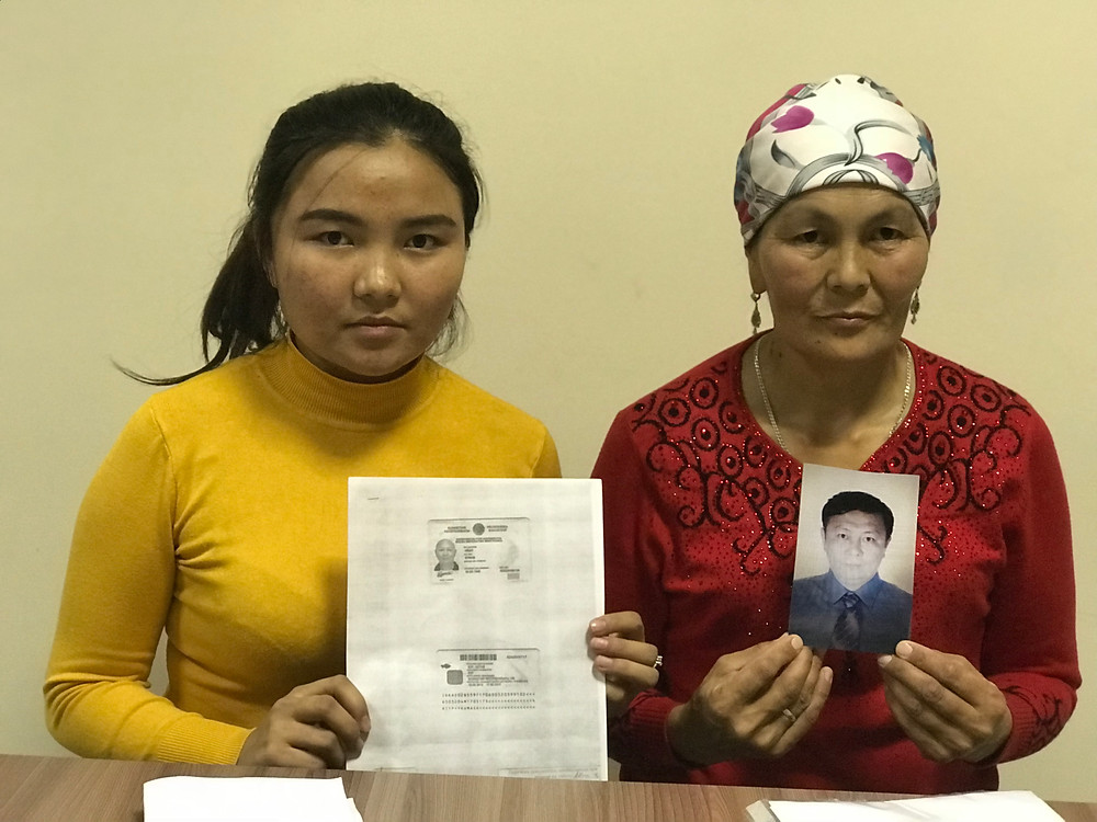 Mikhua Aip (right) holds a picture of her brother Qumash Aip, a long-time engineer at an oil company in Kazakhstan who was sent to a Chinese internment camp in June 2018. @Simina Mistreanu/dpa