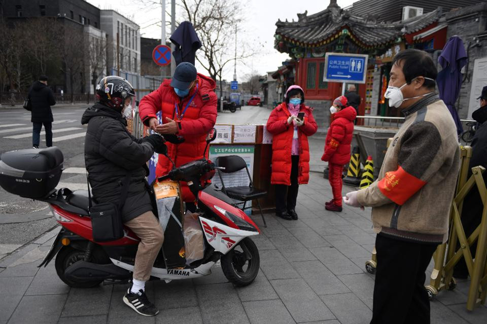 A volunteer checks the temperature of a resident as other volunteers monitor the entrance to a residential community, amid the ongoing COVID-19 coronavirus outbreak in Beijing on March 26, 2020. (Photo by GREG BAKER / AFP) (Photo by GREG BAKER/AFP via Getty Images) AFP VIA GETTY IMAGES