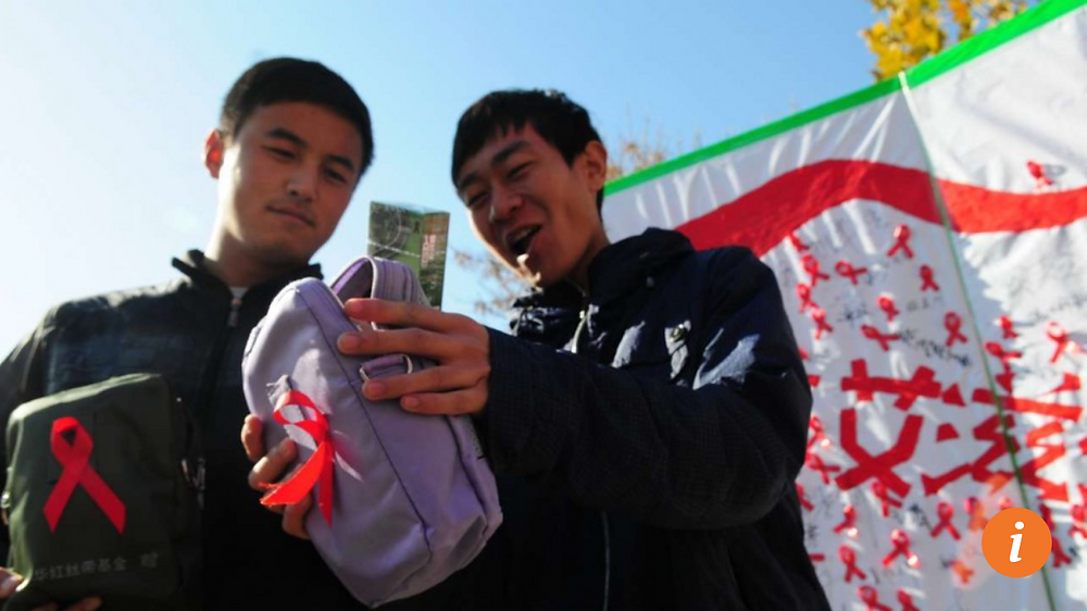 Two Chinese college students show off their World Aids Day Red Ribbon health packs, which include packets of condoms, during a campaign in Liaocheng, Shandong province. Photo: AFP