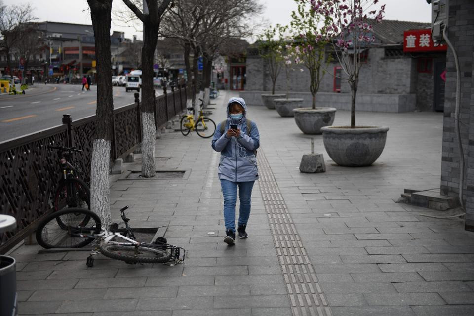 A woman wears a face mask amid the ongoing COVID-19 coronavirus outbreak as she walks on a quiet street in Beijing on March 26, 2020. (Photo by GREG BAKER / AFP) (Photo by GREG BAKER/AFP via Getty Images) AFP VIA GETTY IMAGES