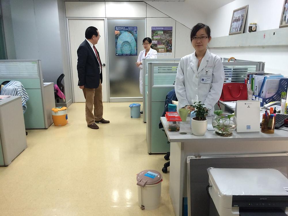 Xu Kecheng talks to PhD students who work as researchers in Fuda Cancer Hospital's laboratories [Simina Mistreanu/Al Jazeera]