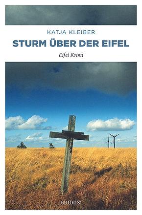 Cover des Krimis Sturm über der Eifel. Man sieht ein Holzkreuz in einem Feld unter dunklen Wolken.