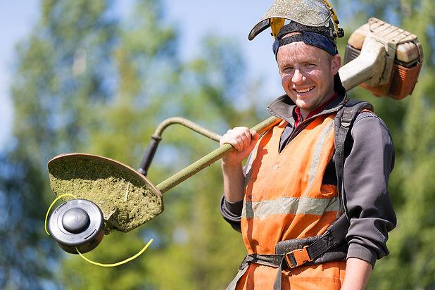Portrait happy gardener or road landscaper man worker with gas grass trimmer equipment.jpg