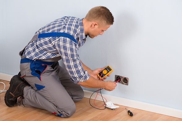Male Electrician Checking Voltage Of Soc
