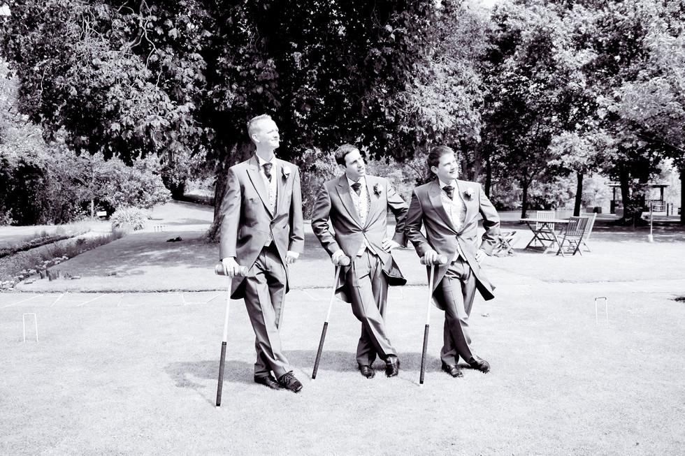Groomsmen resting on croquet mallets