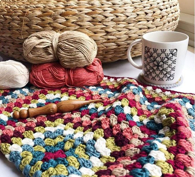 Dear Ewe crochet granny square chart mug next to a granny square crochet blanket in the making