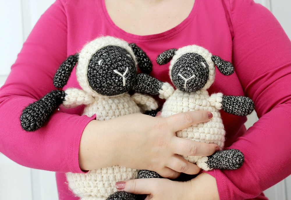 A lady cuddling two crocheted sheep