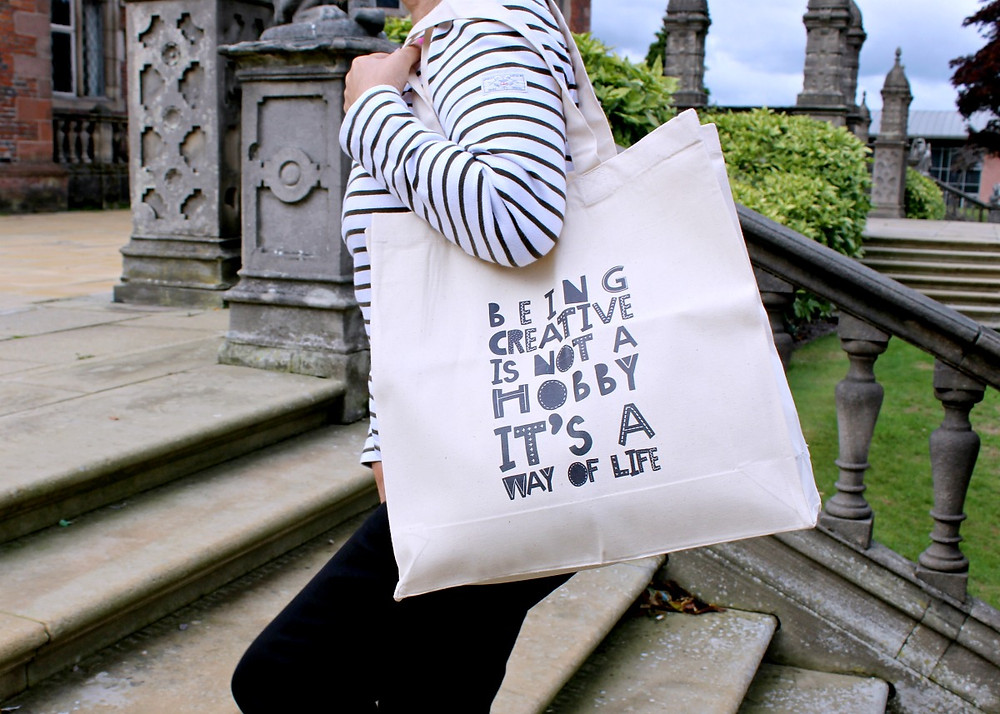 Lady carrying a tote bag which reads Being Creative is not a Hobby it's a way of Life!