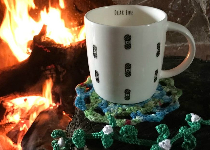 Dear Ewe yarn designed mug next to an open fire