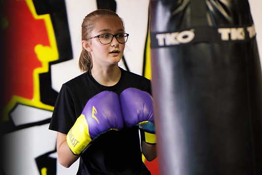 Young woman boxing heavy bag