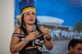 #descriçãodeimagem: Foto de Chirley Pankará. Ela segura um microfone e usa um cocar. Ao fundo, está uma foto do Palácio de Brasília.