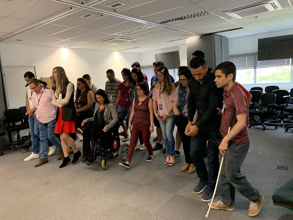 Grupo de pessoas alinhadas em uma sala de treinamento