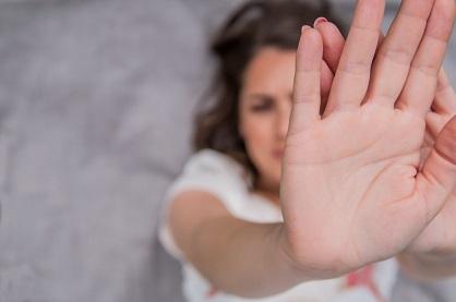 #descriçãodaimagem: foto de uma mulher deitada em um fundo cinza, está com as duas mãos juntas (em primeiro plano) escondendo o rosto da foto.