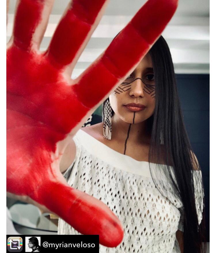 #descricaodeimagem: Dra. Myrian Veloso, ou Krexu, como a chamam na aldeia Rio das Cobras, que significa Lua Crescente, formou-se como médica pela faculdade de medicina da Universidade Estadual do Oeste do Paraná (Unioeste). Ela denuncia o assassinato de lideranças em seu perfil. Na foto, a médica está com o rosto pintado com traços geométricos pretos e a palma da mão direita em destaque, pintada de vermelho bem vivo. Ela tem a pele morena, cabelos pretos compridos e usa franja