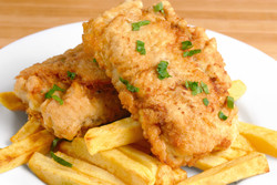 Fried fish and chips on the white plate.