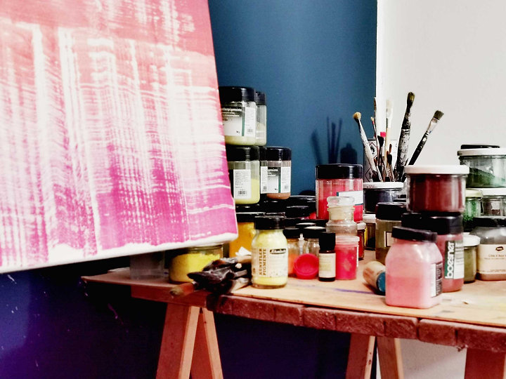 Leinwand und Tisch mit Pigmenten und Pinseln
