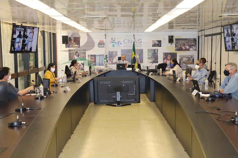 Descrição: Conselheiros sentados ao redor de uma mesa. Televisões do lado direito, esquerdo e a frente do Presidente mostrando as outras pessoas que estão na reunião de forma online.