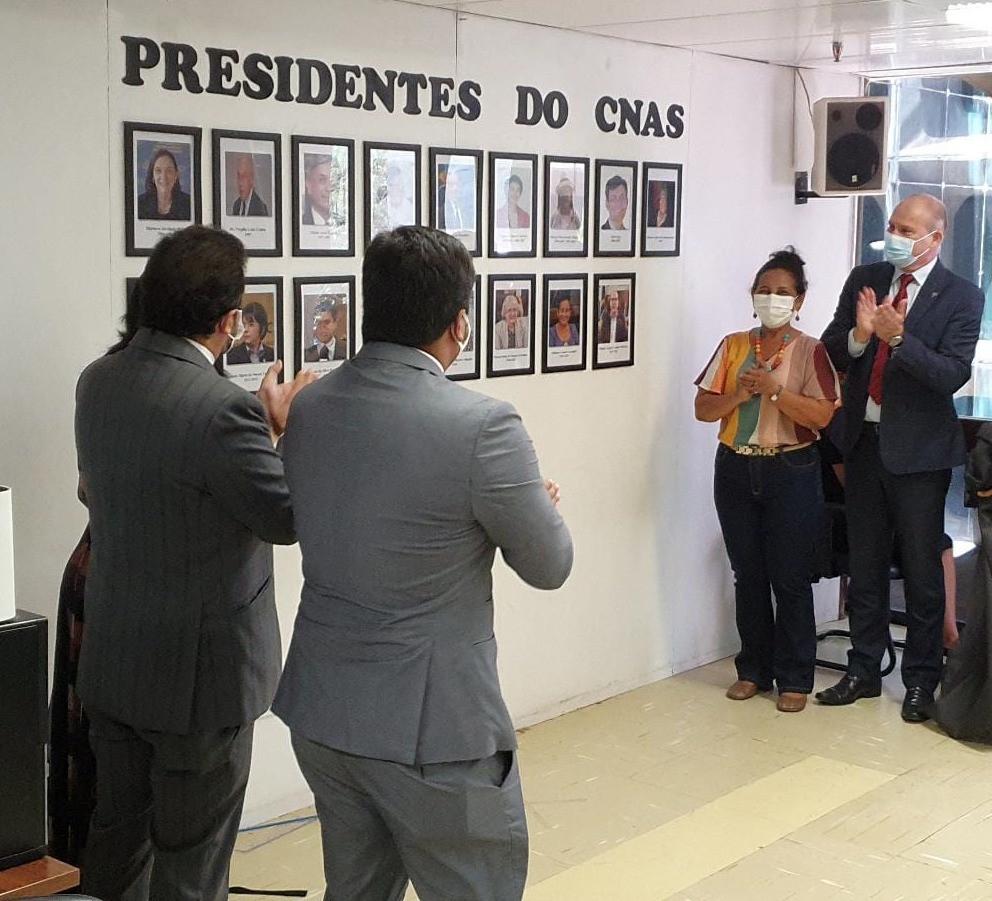 Inauguração da galeria de Presidentes. Quadros com as fotos dos presidentes um ao lado do outro pregados na parede e os Secretários do Ministério do lado esquerdo e a presidência do CNAS do lado direito. Todos batendo palma e olhando para a galeria.