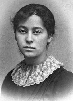 A black and white picture of Amy Levy (1861–1889). She has dark hair and dark eyes, and looks into the camera with a monotone expression.