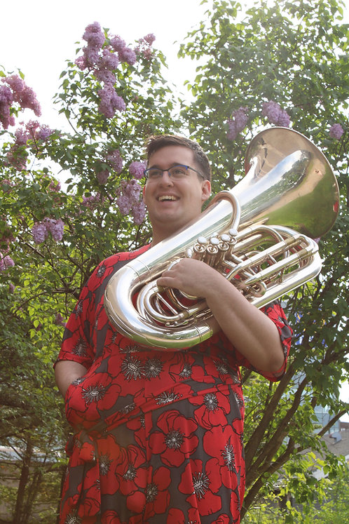 A sunlit white woman laughs, holding a tuba, her other hand in the pocket of her red, flower-print jumpsuit. She has short, dark brown hair and blue glasses. She stands in front of a tree with purple flowers.