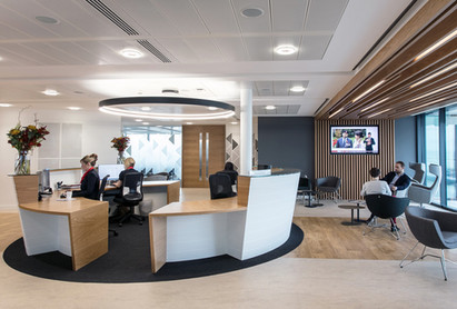 Conical reception counter finished in Crown Cut Oak Veneer and Glacier White Corian®