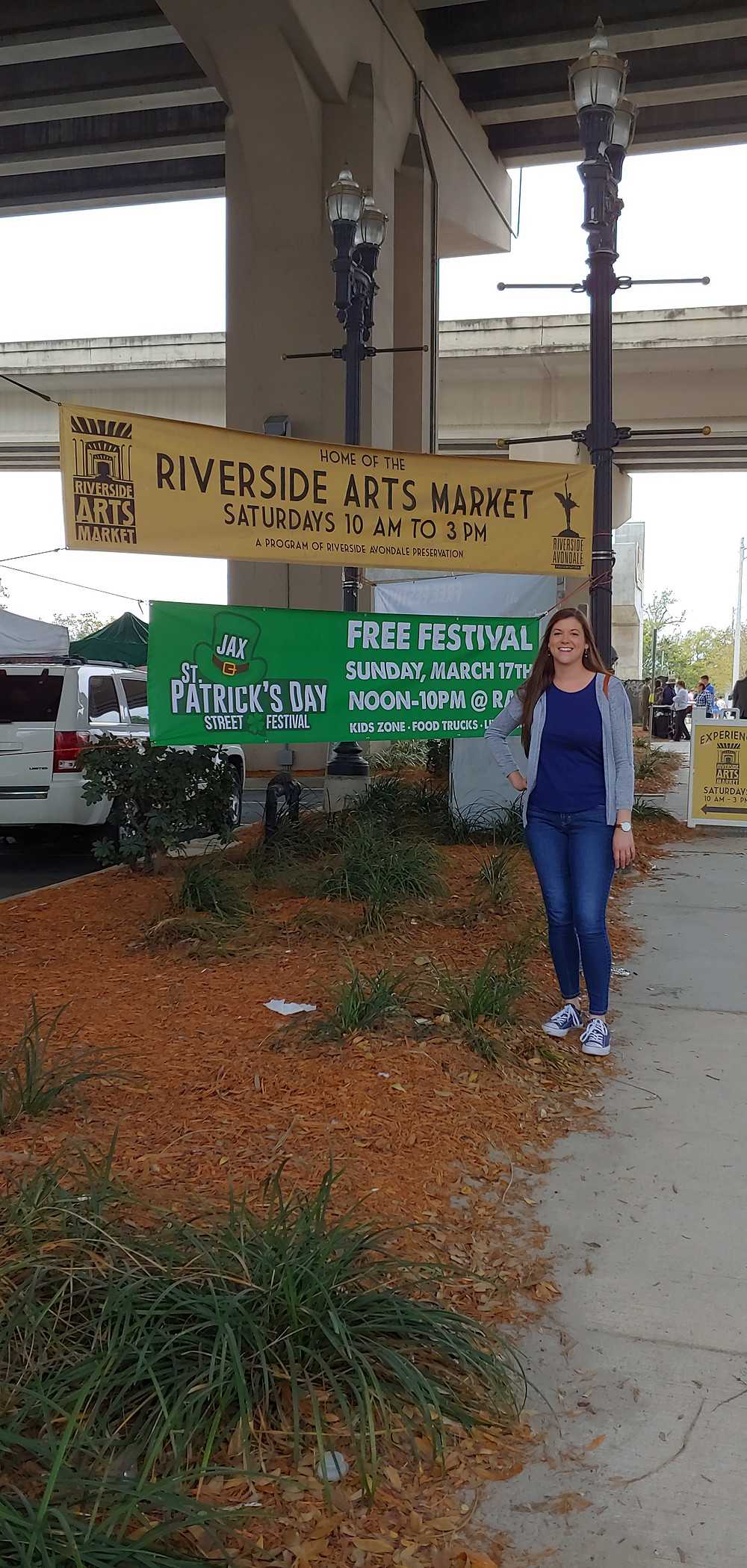 A girl standing outside the Riverside Arts Market entrance.