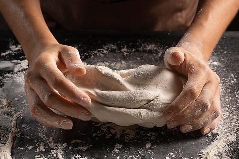 high-angle-chef-kneading-dough-with-hand