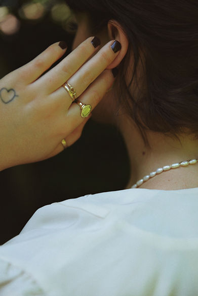 Alice Catherine is wearing our vintage large oval statement signet ring with other vintage rings and pearls .