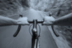 Handle bars of a bike going downhill on a road