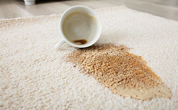 Photo of a cup of coffee spilled on white carpet