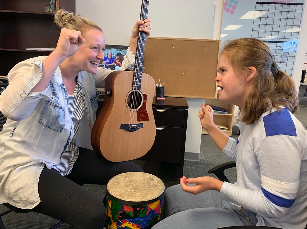 Uma a dolescente com Trissomia do 21 se diverte junto a uma adulta que está segurando um violão