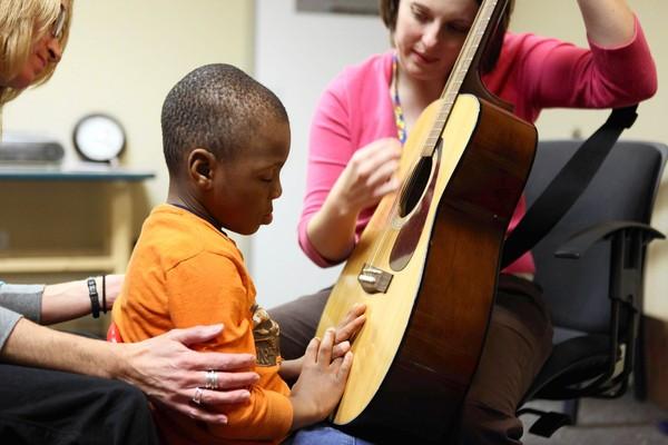 Uma criança de olhos fechado mantem cointato com as mãos no tampo do violão para sentir a vibração do som enquanto outra pessoa o toca