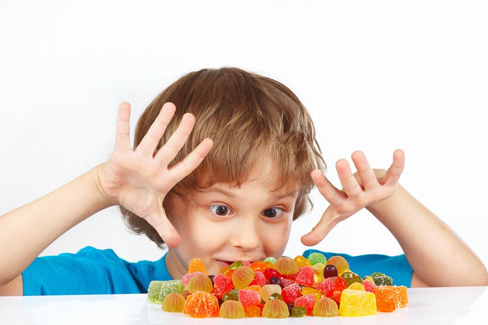 """Criança olhando ficamente para um prato cheio de doces coloridos praticamente falando: """"my precious""""!"""