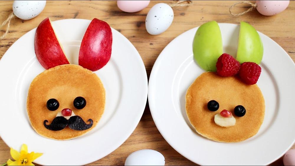 dois pratos com panqueca e frutas que estão dispostas formando coelhinhos fofinhos