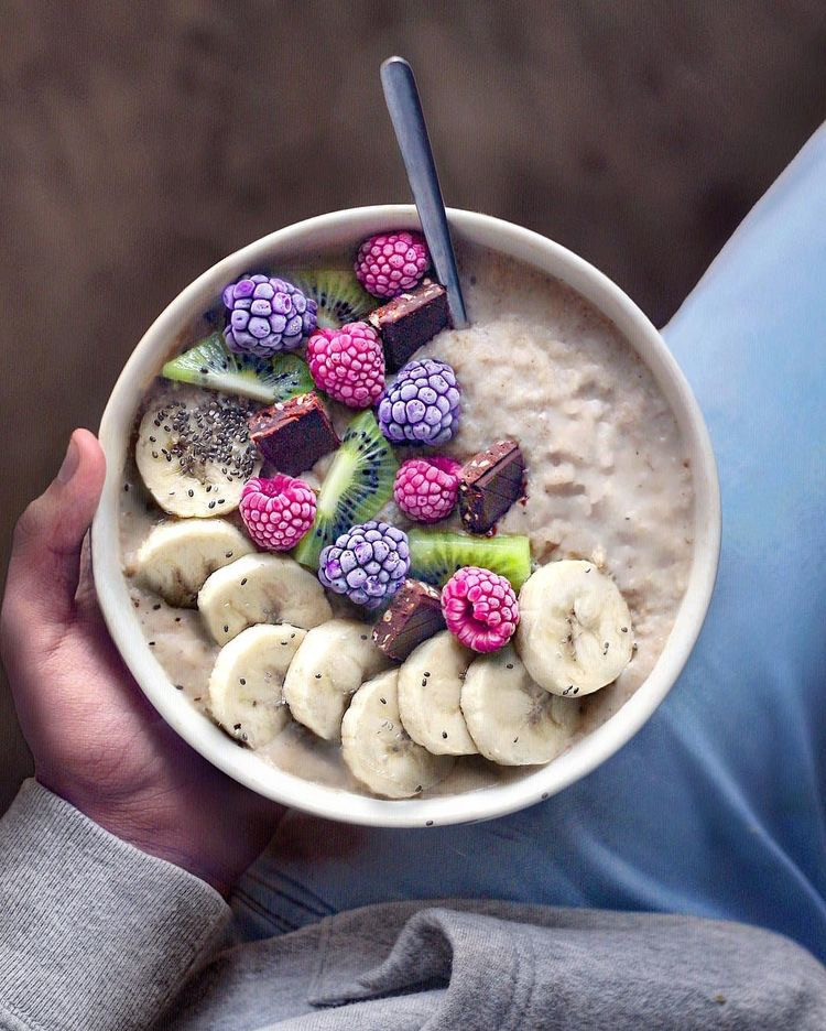 A bowl of oatmeal with chocolate, banana, and berries