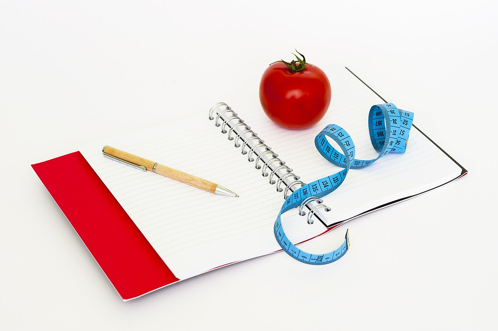 A journal with a pen, tomato, and a tape measure.
