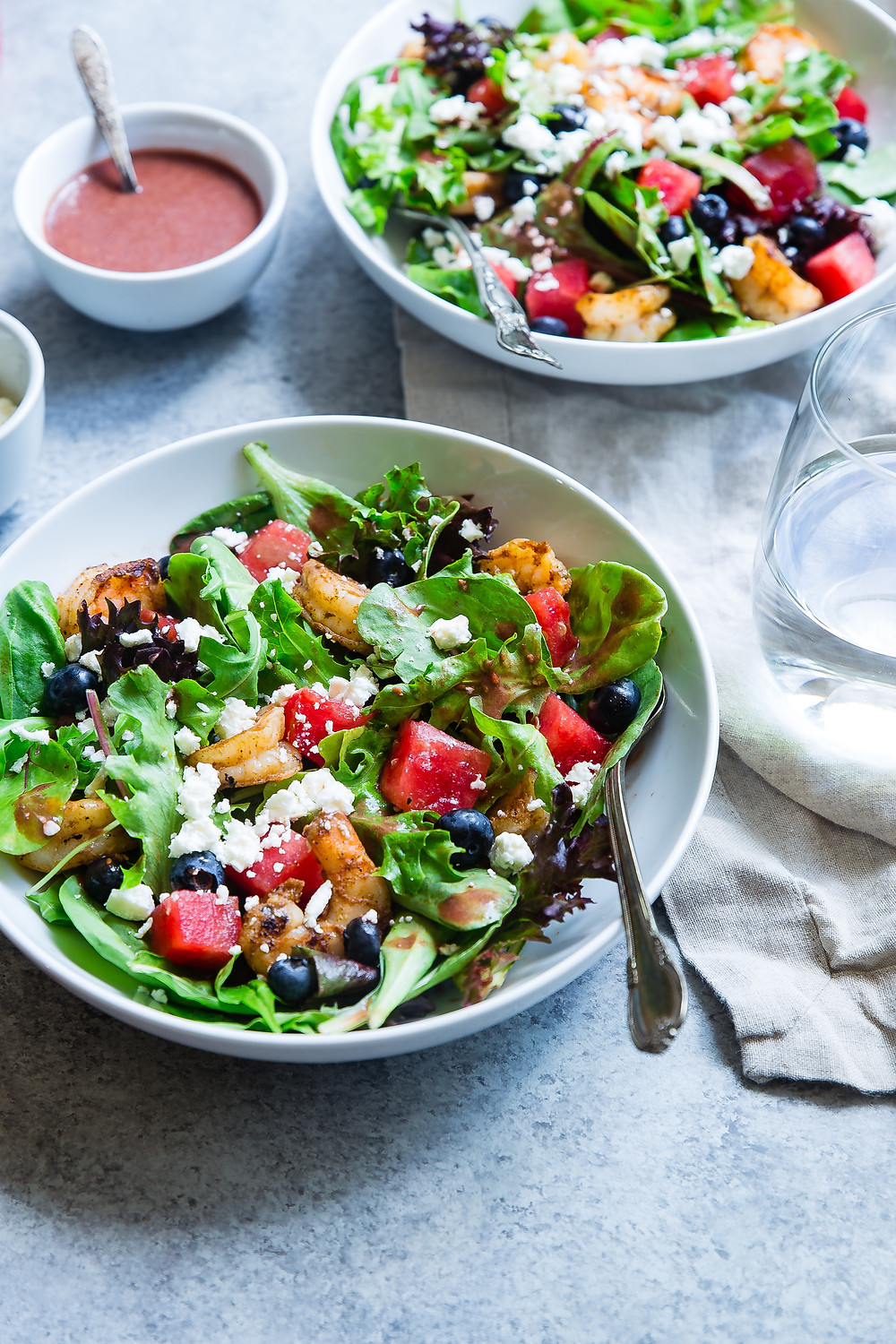 Two colorful salads with fruit and cheese.